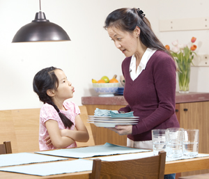 Mother trying to get young obstinate daughter to set the plates on table.