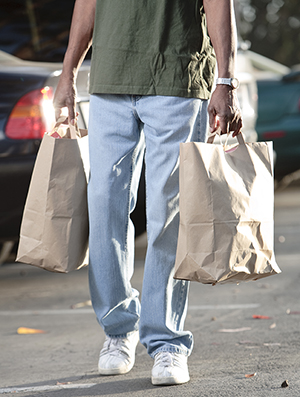 Man carrying groceries in bags with handles.
