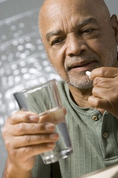 Man putting a pill in his mouth with one hand and holding a glass of water with the other hand.