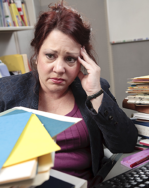 Woman in office looking stressed.