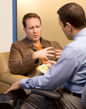 Man sitting and talking to health care professional.