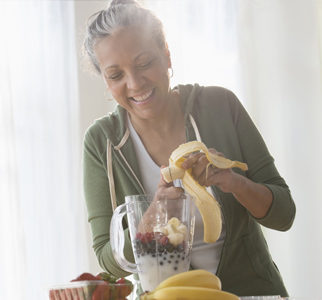 Woman using a blender to make a fruit smoothie
