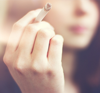 Close-up of a woman's hand holding a burning cigarette